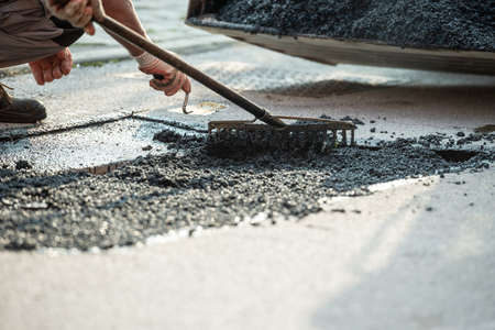 Closeup view of worker using rakes to arrange fresh asphalt on the road that is being repaired.