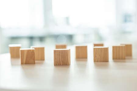 Holzklötze, die zufällig auf den Schreibtisch gelegt werden. Konzeptionelle Geschäftsvision und Herausforderung.