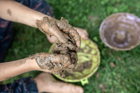 Top closeup view of toddler child playing with mud having his hands all messy.