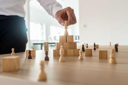 Concetto di gerarchia aziendale con l'uomo d'affari che posiziona la figura degli scacchi del re in cima a blocchi di legno impilati in legno e altre figure sparse sulla scrivania dell'ufficio.