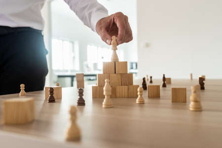 Business hierarchy concept with businessman placing chess figure of king on top of wooden stacked wooden blocks and other figures spread on office desk.
