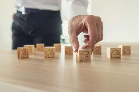 Imagen retro del empresario arreglando bloques de madera con el icono de la casa sobre ellos en el escritorio de la oficina. Foto de archivo