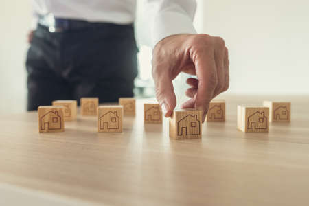 Retro image of businessman arranging wooden blocks with house icon on them on office desk. Stock Photo - 110301321