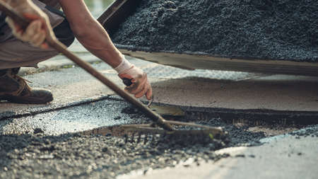 Retro image of two workers working together to lay new asphalt on damaged road with one spreading and arranging the cement mix and the other leveling it.