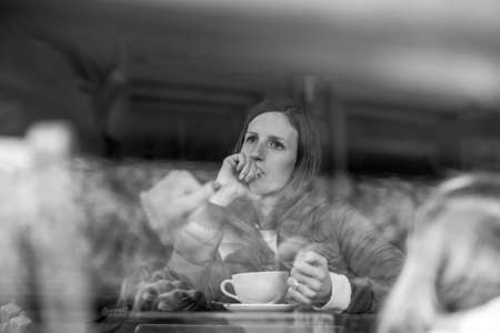Greyscale image of a young woman sitting alone in coffee shop thoughtfully leaning on her hand.