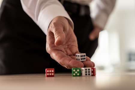 Business risk concept - businessman throwing dices on office desk.