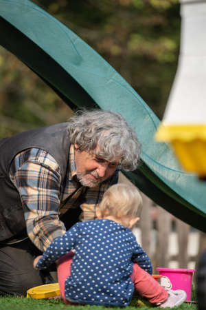 Grandpa and granddaughter playing outside in playground sitting on the grass. Stock Photo