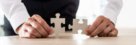 Wide view image of businessman holding two matching puzzle pieces. Conceptual of business vision and solution.