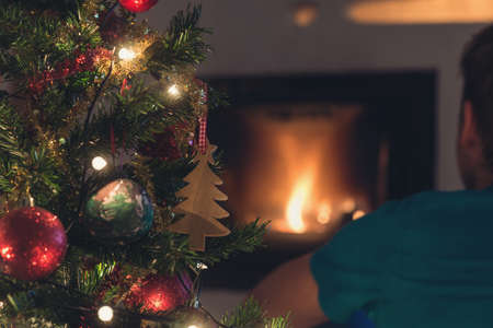 View from behind of young man sitting in front of fireplace with fire and Christmas tree next to him.
