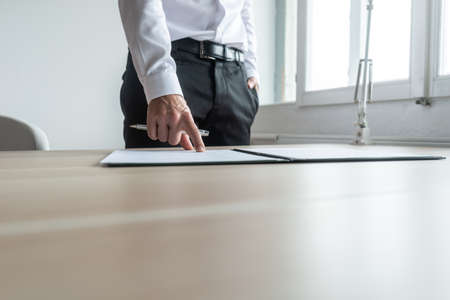 Businessman standing at his desk pointing to a document in folder where to sign.