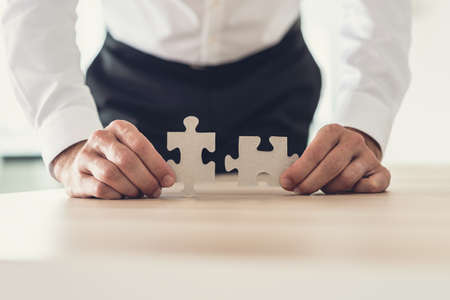 Front view of businessman holding two matching puzzle pieces leaning on his office desk. Archivio Fotografico - 126347180