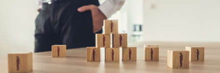 Retro vintage image of businessman standing next to an office desk with wooden cubes with people icons placed in  a pyramid.