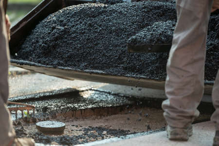 Construction workers applying gravel and cement to a bump in the road to make new asphalt pavement.