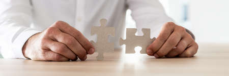Wide view image of a businessman sitting at his desk holding two matching puzzle pieces. Stock Photo