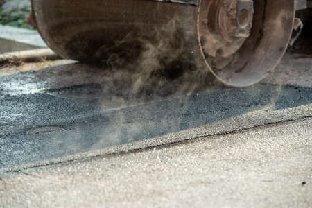 Closeup of a roller going over fresh asphalt with steam rising from the concrete. Stock Photo
