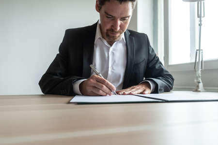 Businessman or lawyer sitting at his office desk signing document or contract in a binder.