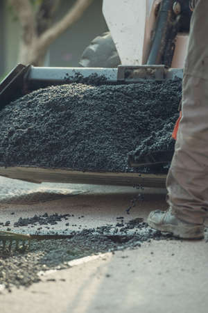 Retro image of a worker taking asphalt mix with a shovel from a wheelbarrow to patch a bump on the street.