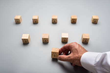 View from above of a businessman arranging wooden cubes with people icon on grey background. Conceptual of human resources.