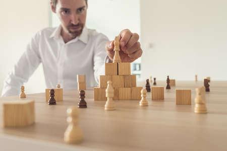 Giovane uomo d'affari serio che posiziona il pezzo degli scacchi del re in cima alla piramide fatta di cubi di legno su una scrivania dell'ufficio con altri pezzi degli scacchi posizionati su di esso. Con effetto filtro retrò.