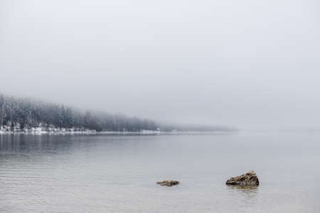 Two rocks peeking out calm winter lake with forest in background on a foggy day. Banco de Imagens