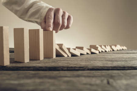 Businessman stopping collapsing wooden dominos with his finger. Conceptual of business crisis solution.