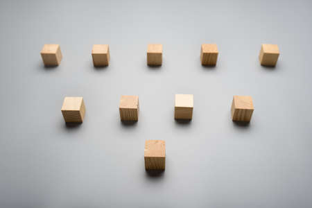 Ten blank wooden cubes placed over grey background in a triangle shape.