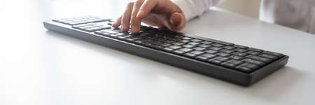 Wide view image of programmer or businessman typing on black computer keyboard using one hand.