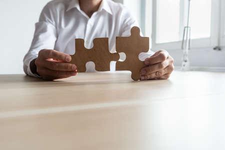Vorderansicht eines Geschäftsmannes, der an seinem Schreibtisch sitzt und zwei passende Puzzleteile mit Kopienraum im unteren Teil des Bildes hält.