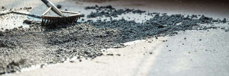 Wide view image of rakes arranging fresh asphalt mixture to cover and repair a crack in the road. Stok Fotoğraf