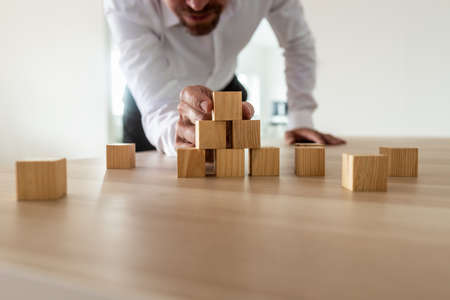 Geschäftsmann, der sich hineinlehnt, um die Pyramidenform mit leeren Holzblöcken auf dem Schreibtisch sorgfältig zusammenzubauen. Konzeptionelle Unternehmensgründung und Vision.