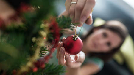 View from above of a woman placing red holiday bauble on Christmas tree with focus to he ball.