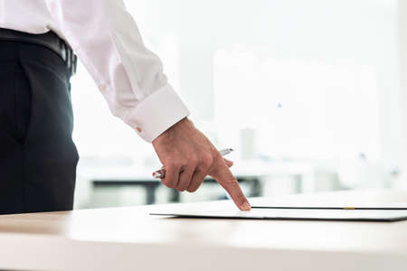 Businessman standing at his office desk pointing to a document, application or contract holding a pen. Stock Photo