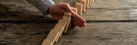 Wide view image of businessman stopping domino effect with his hand on rustic wooden desk.