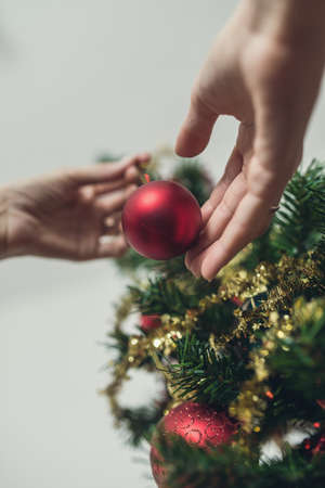 Low angle view of female hand placing red holiday ball on Christmas tree. With retro filter effect.
