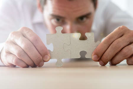 Businessman merging together two matching puzzle pieces leaning on his office desk. Banco de Imagens