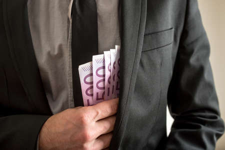 Bribery concept - closeup of businessman putting five hundred Euro bills in the inner pocket of his suit jacket.