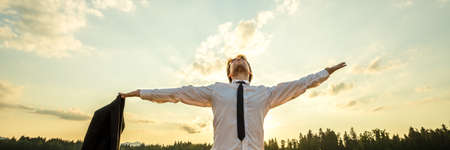 Powerful young businessman standing under evening sky with his arms wide open as he celebrates his success. Фото со стока