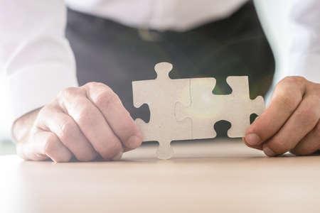 그의 사무실 책상에 기대어 두 개의 결합된 퍼즐 조각을 들고 사업가의 근접 촬영 보기.