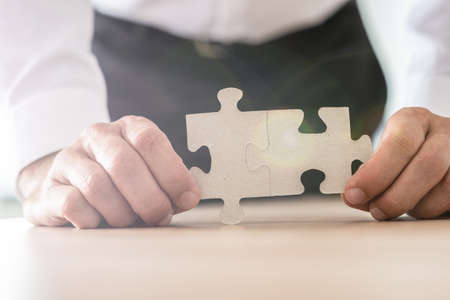 Closeup view of businessman holding two joined puzzle pieces leaning on his office desk. Stockfoto - 113035342