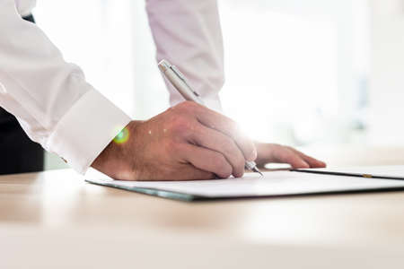 Businessman signing contract or application form leaning on his office desk. Stockfoto