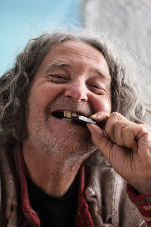 Happy senior man with missing teeth smiling as he bites in to a piece of chocolate. Standard-Bild