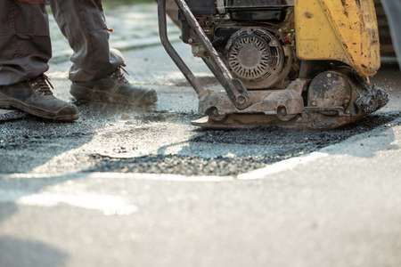 Worker using compactor to finish patching bump in the road with fresh asphalt. Archivio Fotografico - 113034999