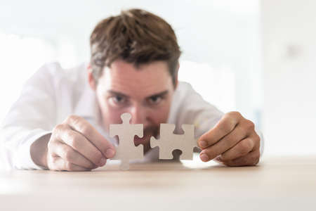 Young businessman leaning on his office desk joining two matching puzzle pieces.