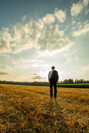 Businessman standing with his back to the camera in the sawn field under evening sky with his suit jacket over the shoulder.