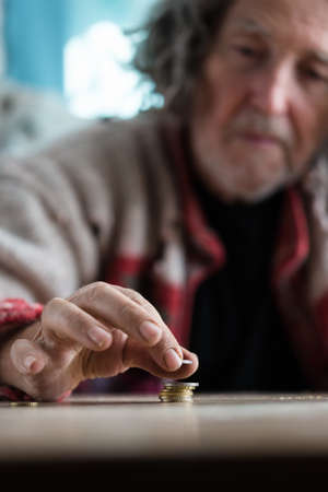 Senior homeless man stacking and counting coins on desk in a conceptual image. Stock Photo