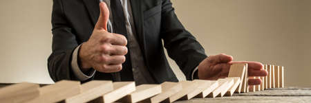 Wide view image of businessman showing thumbs up sign as he stops the dominos from falling with his hand in a conceptual image.