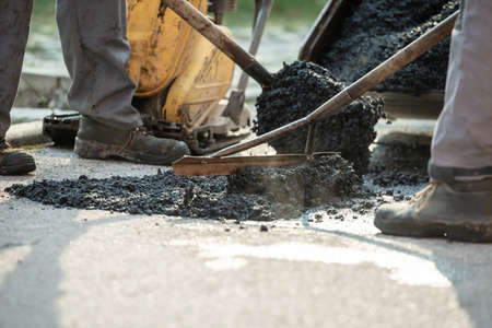 Two construction workers working together to patch a bump in the road with fresh asphalt. Stock Photo