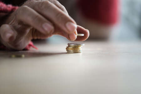 Closeup of male senior hands stacking Euro coins. Conceptual of poverty and personal crisis.
