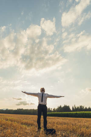 Businessman with his arms wide open standing under cloudy evening sky in sawn field. Conceptual of business vision and power.