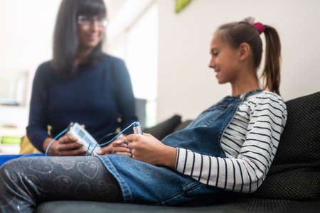 Female bioresonance therapist with her young girl client holding zapper electrodes.
